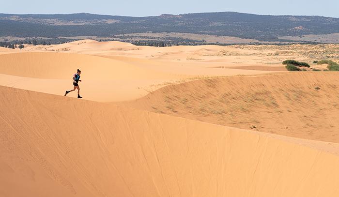 Brooks Ambassador Jacqui Bell runs down a sand dune.